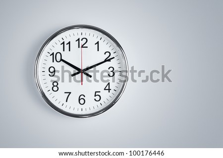 Silver shiny clock hanging at the wall with copy space - stock photo
