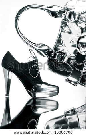 Silver shopping. Fancy black and silver shoe with a silver bag on a reflective mirror surface in high contrast. - stock photo