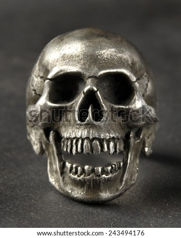 Silver skull ring on black background