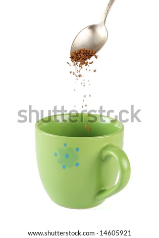 Silver spoon and instant coffee granules going into cup isolated on white - stock photo