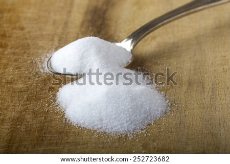 Silver spoon of baking soda over wood background - stock photo