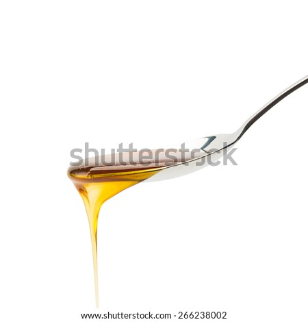 silver spoon with golden honey that runs down - stock photo