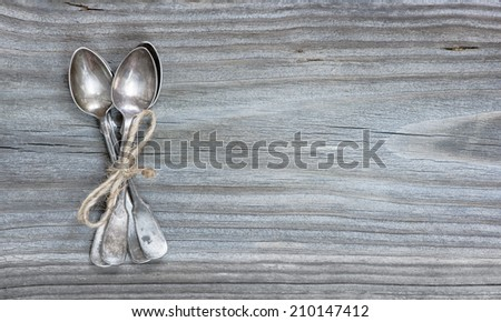 Silver spoons on a wooden board - stock photo