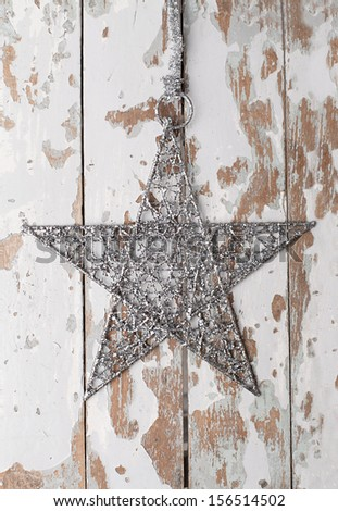 silver star hanged on white old wooden door - stock photo