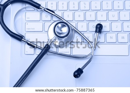 Silver stethoscope over laptop keyboard - stock photo