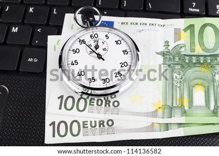 Silver stopwatch on black laptop keyboard with 100 euro bills - stock photo