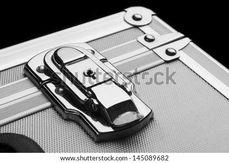 silver suitcase on a black background - stock photo