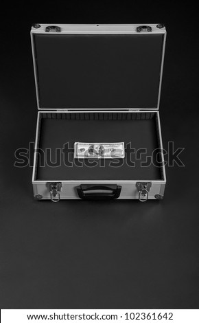 silver suitcase with a bunch of money on a black background - stock photo