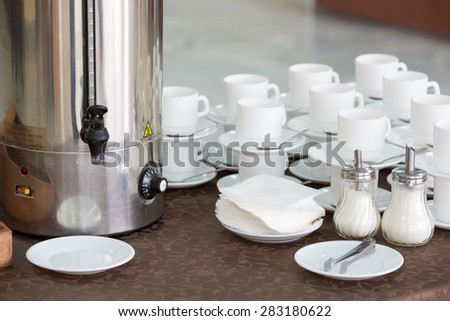 silver tea urn, white cup and saucer and sugar bowl - stock photo