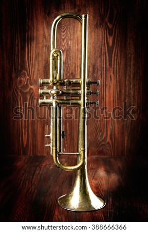 Silver trumpet on wooden background - stock photo
