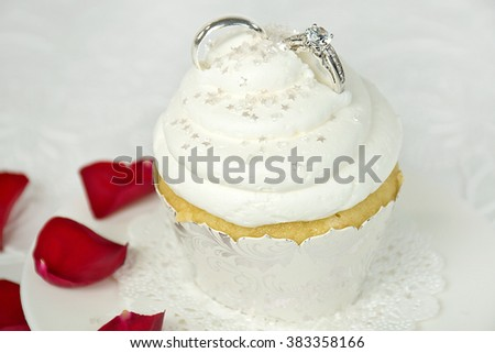 silver wedding rings in cupcake icing with star sprinkles and red rose petals - stock photo