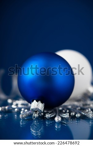 Silver, white and blue christmas ornaments on dark blue background with space for text.  - stock photo