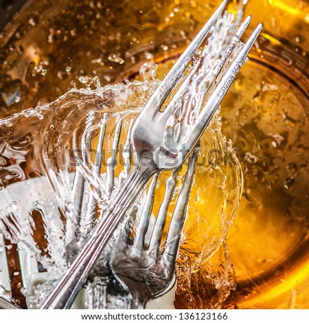 Silverware and glass dishes washed with splashing water - stock photo