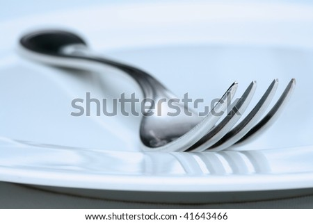 silverware and plate-extreme closeup of a fork - blue tint - stock photo