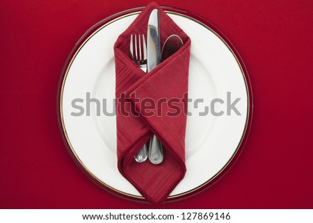 Silverware red napkin on a white plate - stock photo