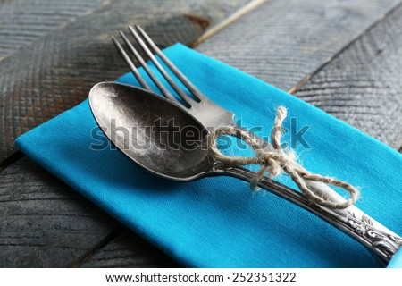 Silverware tied with rope on colorful napkin and wooden planks background - stock photo