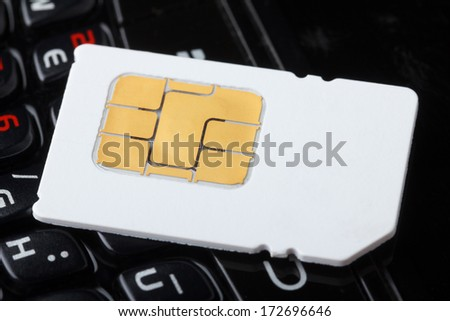 Sim card on cell phone keyboard - stock photo