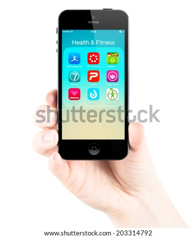 SIMFEROPOL, RUSSIA - JULY 05, 2014: Female hand holding a black Apple iPhone 5S device with popular health and fitness applications on screen. - stock photo