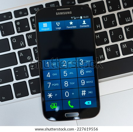 SIMFEROPOL, RUSSIA - NOVEMBER 01, 2014:  Keypad of Samsung Galaxy S4 over Apple Macbook Pro keyboard. Samsung Galaxy S4 is an Android smartphone produced by Samsung Electronics. - stock photo