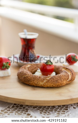 simit, tea, cherry tomato and cheese at balcony on a circle wooden plate front view - stock photo