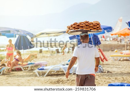 Simit vendor (seller of sesame-encrusted bread rings, Turkish bagels) with a heap of simits on a plate on his head walking through a sunny beach in Alanya, Turkey. - stock photo