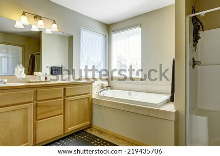 Simple bathroom interior with bath tub in the corner and two windows