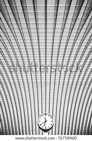 Simple black and white clock in front of conceptual modern interior with steel arches in perspective - stock photo