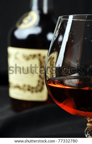 Simple composition of glass and bottle cognac. black background - stock photo