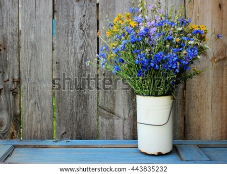 Simple composition with bouquet of blue wild cornflowers in an old rusty top on vintage grey wooden background. Floral decor elements. Concept for greeting card for valentine, birthday or mothers day
