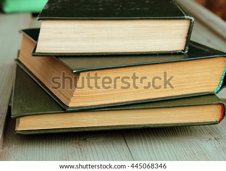 Simple composition with stack of old books with green cover on aged wooden table. Vintage design
