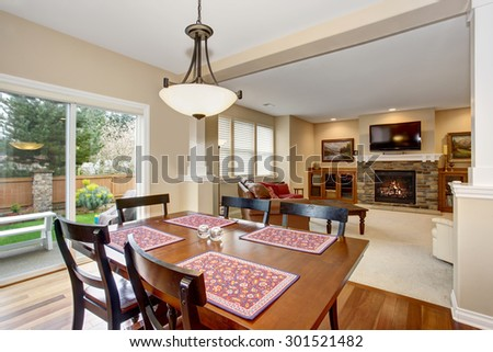 Simple dinning area with connected living room and hardwood floor.