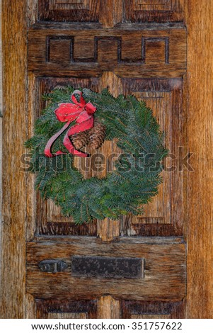 Simple festive Christmas wreath on old wooden door at Christmastime - stock photo