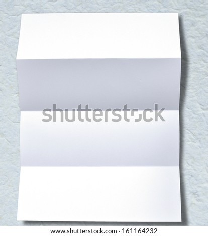 Simple folded white blank paper on background.