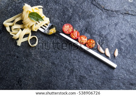 Simple food. Pasta seria. Close up of italian pasta rolled on a fork, cherry tomatoes and garlic on black stone background