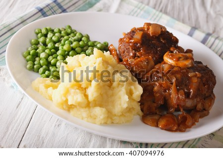 Simple Food: Salisbury steak with mashed potatoes and green peas close-up on a plate on the table. horizontal