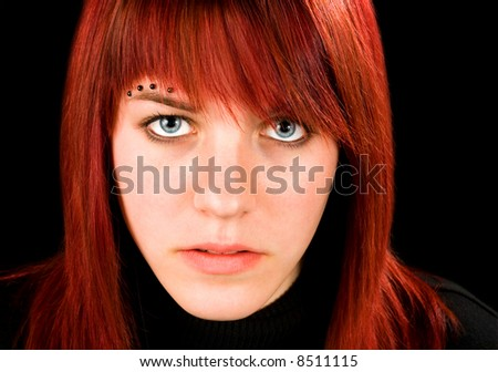 Simple frontal shot of a beautiful pierced redhead girl staring at the camera. Studio shot. - stock photo