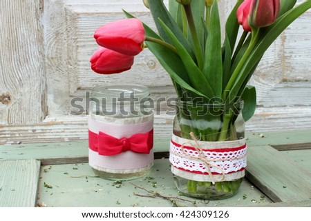 Simple glass cans decorated with cloth, ribbons, lace and jute and bouquet of fresh red tulips. Rustic decor elements - stock photo