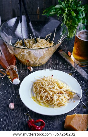 Simple homemade italian pasta recipe: spaghetti with garlic, chilli and olive oil. Arugula leaves on pasta. Parmesan, olive oil bottle and grater near plate. Dark wood background. - stock photo