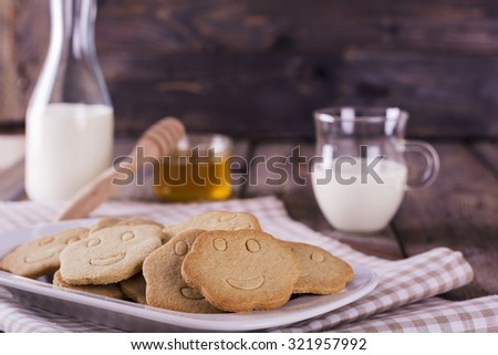Simple homemade shortbread cookies with  glass milk and honey on an old wooden table background.Toned image. Selective focus.