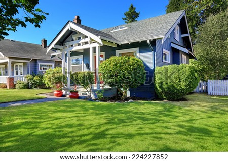 Simple house exterior with tile roof. Entrance porch with front yard landscape