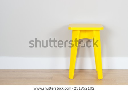 simple interior with a yellow stool and copy space on the wall - stock photo