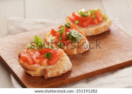 simple italian appetizing bruschetta with tomato and basil, on old table - stock photo