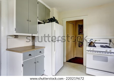 Simple kitchen interior with white stove and refrigerator in old house