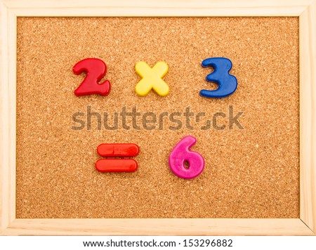 Simple mathematic multiplication on a wooden frame cork board - stock photo