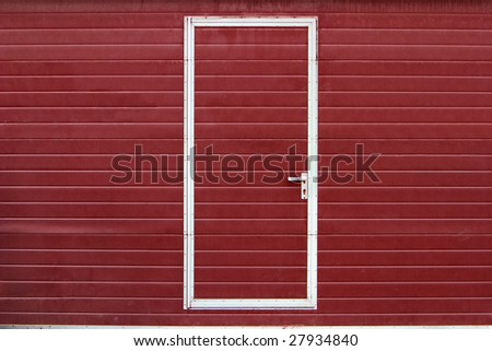 simple metal door in red wall - stock photo