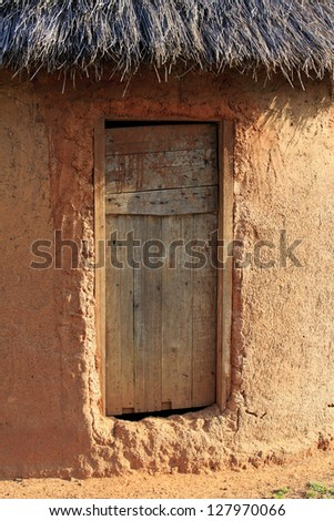 Simple mud hut with a wooden door - stock photo