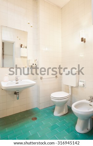 Simple, old bathroom with green tiled floor - stock photo