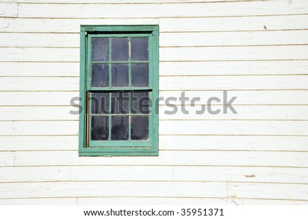 Simple old white painted wooden building with green trimmed windows - stock photo