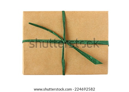 Simple parcel wrapped in brown paper with green ribbon knot - isolated on white - stock photo