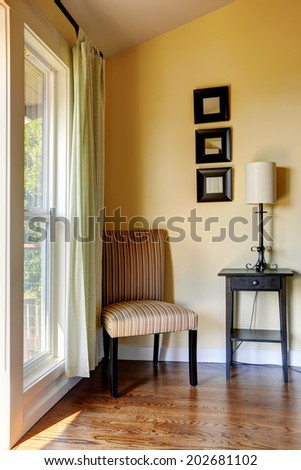 Simple room corner furnished with striped chair, small table and lamp. - stock photo